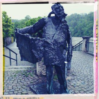 Eine Bronzeskulptur, die ihren Mantel öffnet, was so ähnlich aussieht wie der klassische Exhibitionist.