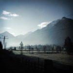 Gegenlichaufnahem in den Bergen. Im Morgendunst sieht man einzelne Nadelbäume auf Wiese vor hohen Bergen im Hintergrund, sowie einen Strommast. Monochromes Bild, etwas blaugräulich gefärbt.
