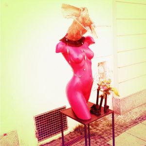 Eine lila Schaufensterbüste ohne Kopf und ohne Beine. Farbverfremdetvor gelblicher Hauswand und sparsam geschmückt.
