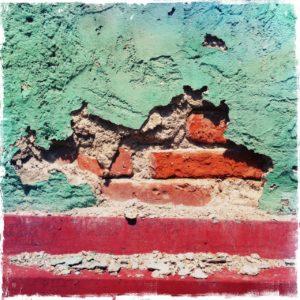 Eine Wand in übersättigten Farben, hellblau über Rot. Der raue Außenputz hat ein großes Loch, durch das die Backsteine zu sehen sind