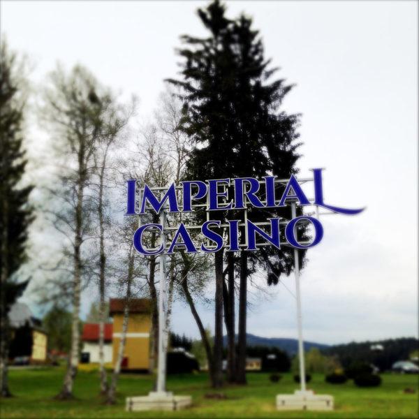 Vor einer Fichte steht ein großes blaues Imperial Casino Letternbanner auf zwei Pfosten. Dahinter Gebäude.