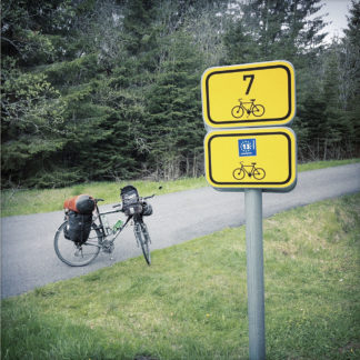 zwei etwa Din A 4 große gelbe Radwegschilder an einem Pfosten vor dem bepackten Fahrrad im Wald