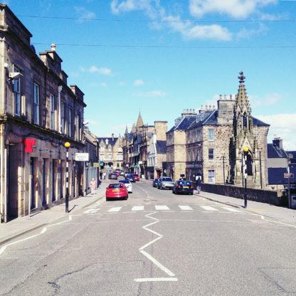 Straßenszene in der schottischen Stadt Tain. Mittig fluchtend blickt man eine Straße entlang. Ein rotes Auto schiebt sich ins Bild, gothisch anmutende Zierart an den bleichen Hauswänden.