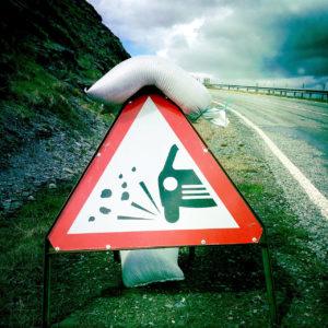 Mit einem Sandsack gegen Windböen geschütztes Warnschild, auf dem ein Autosymbol Steine schleudert.