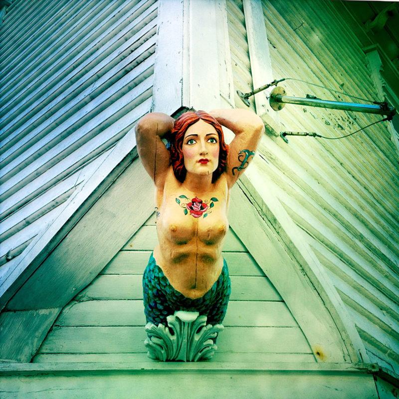 Eine Galionsfigur, weiblich, reckt sich baren Oberkörpers an einer hölzernen Hauswand, die aussieht wie der Bug eines Schiffes. Sie hat die Arme hinter dem Kopf verschränkt