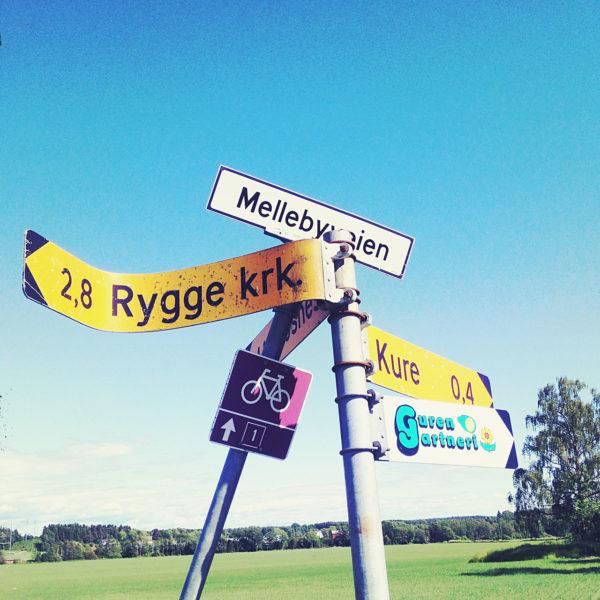 Schildergewirre in blassblau mit gelb. Ein verbogenes Schild zeigt nach Rygge KRK, der Rygge-Kirche in Norwegen.