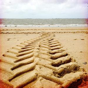 Eine Traktorspur führt gezackt durch Sand aufs Meer zu