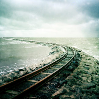 In einer linkskurve führt eine Schmalspurbahnstrecke ins Meer und verschwindet in wilder Gischt.