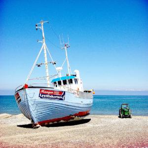 Links im Bild ein hellblaues Boot mit roter Zierfarbe auf dem Strand. Rechts daneben ein winzig anmutender alter Traktor.
