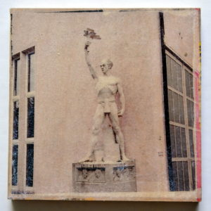 eine heroische Figur in Pastellfarben fast weiß vor der Fassade eines Wasserkraftwerks.