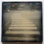 Ein gekrümmter, sehr langer Zebrastreifen führt über einen Parkplatz auf ein längliches Hinweisschild zu.