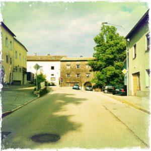Blick eine Dorfstraße etwas aufwärts auf eine Häuserfront zweier aneinander gebauter Häuser zu. Im Vordergrund ein Kanaldeckel.