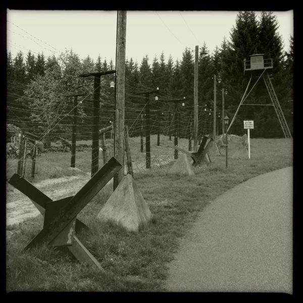 Schwarz-weiß-Bild einer Grenzbefestigung mit Stacheldrahtverhau und Wachturm vor Fichtenwald.