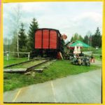 Das gelb umrahmte Bild zeigt einen rötlichen, hölzernen Bahnwagon auf einer endenden Linie, daneben eine Picknick-Bank