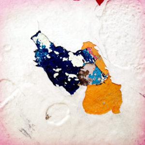 Ein bunter Klecks auf weißer Wand, der durch abblätternde Farbeschichten entstanden ist.