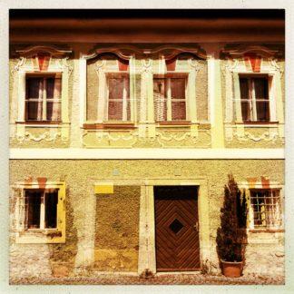 Blick auf eine überblendete, bräunlich verfärbte Hauswand mit fenstern und Tür.