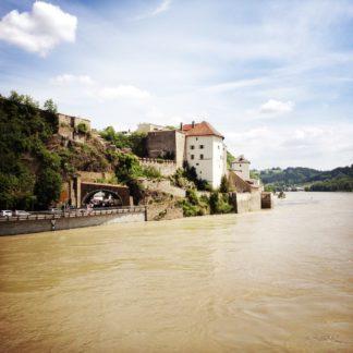 Blick über die Donau auf ein stattliches Gebäude über einem Straßentunnel.