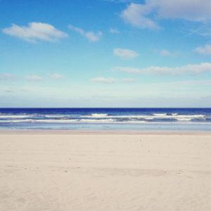 Ein sehr sparsames Landschaftsbild, das in Schichten von unten nach oben hellen Sand, Wellen, tiefblaues Meer, nach oben hin dunkler werdender helbblauer Himmel mit weißen Wolken zeigt