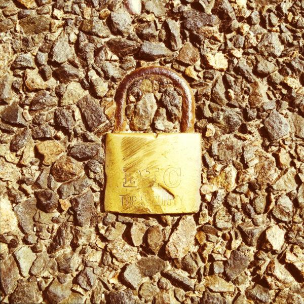 Draufsicht auf ein goldgelbes, abgewetztes Vorhängeschloss, das sich im rauen Split-Teer plattgefahren einfügt.