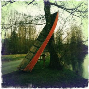 Ein auf dem Heckk stehendes etwa drei Meter langes Boot wird von einem Baum durchwachsen und bildet eine skurile Einheit.