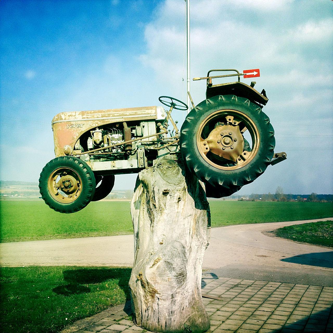 Auf einem Baumstumpf ist ein alter Traktor etwa anderthalb Meter hoch schwebend angebracht.