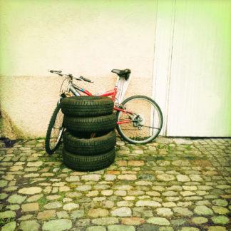 Ein Stapel abgefahrener Reifen, vier Stück vor einem Fahrrad, das an einer Hauswand lehnt.