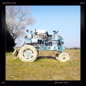 Eine blaue Maschine, die einem hochgelegten Traktor ähnelt auf weitem Feld. Links im Bild ein Gebüsch.