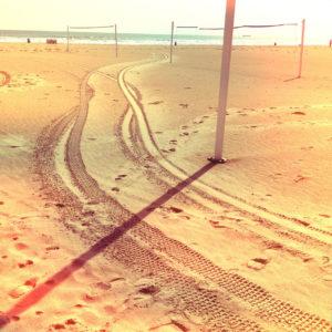 Zwischen Beachvolleyball-Feldern führt eine Reifenspur über den Strand. Der Pfosten eines Netzes wirft einen markanten Schattenin die linke untere Ecke des Bildes.