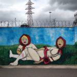 Vor einem etwa ein drittel des Bilds einnehmenden Himmel mit dunklen Wolken und Strommast ist auf einer Stacheldraht bewehrten Mauer ein Graffiti mit zwei liegenden, schlummernden Matruska-ähnlichen Frauen gesprayt.