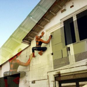 Das überbeldente Bild einer Hauswand, an der eine lebensgroße Figur des Comic-Helden Spiderman montiert ist in typischer, hockender, lauernder Position, aufwärts kletternd.