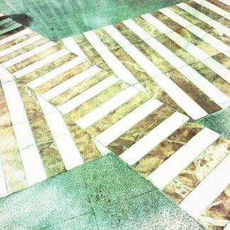 Zwei sich kreuzende Zebrastreifen auf grünlich vignettierter Teerfläche.