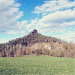 Ein pyramidenähnlicher Berg, dessen Gipfel von einem markanten Felsen gekrönt ist. Unten junge, grüne Wiese, oben Himmel mit Schönwetterwolken.