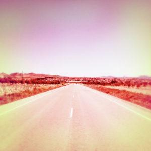 Ein rötlich verfärbtes, quadratisches Foto aufgenommen auf der Mitte der Straße in Richtung Flucht. Im Hintergrund ein paar Häuser und eine Hügelkette.