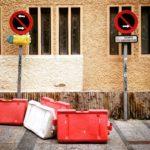 Zwei Parkverbotsschilder rechts und links im Bild vor einer Hauswand. Spanische Aufschrift. Dazu einige weiße und rote mobile Barrieren als chaotisches Ensemble.