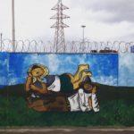Vor einem etwa ein drittel des Bilds einnehmenden Himmel mit dunklen Wolken und Strommast ist auf einer Stacheldraht bewehrten Mauer ein Graffiti mit zwei liegenden, schlummernden Menschen gesprayt. Ein Landarbeiter und Landarbeiterin.