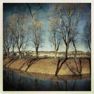 Linkes von drei Bildern, die quer zu einem kanalisierten eingeböschten Fluss aufgenommen wurden. Auf der Böschung steht dystopisch düster eine unbelaubte Platanenallee.