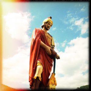 Aus der Froschperspektive sieht man eine Römerfigur vor blauem Himmel mit weißer Bewölkung. Roter Umhang, Helm und Schwert, Kopf geneigt, als wäre er erschöpft.