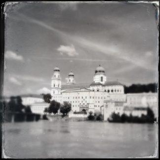 Über en Inn hinweg blickt man auf Passaus Dom mit drei gut sichtbaren Türmen mit runden Kuppeln. Das quadratische Schwarz-weiß-Bild ist im Retrostil mit auffransenden Rändern. Markant der Himmel unter Zirruswolken.