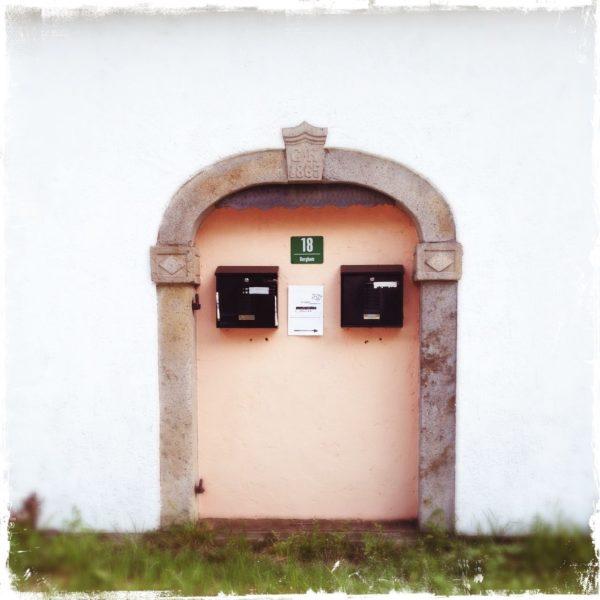 Unter einem zugemauerten Korbbogen hängen zwei Briefkästen und ein Hausnummernschild an blassrosa verputzter Wand.