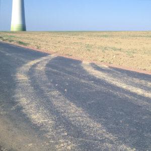 von einem Teerweg, der die linke Ecke des Bilds fast diagonal von Ecke zu Ecke einnimmt, schwingt sich eine erdige Reifenspur in einer Rechtskurve auf ein karges Feld. Links oben am Horizont fußt ein Windrad.