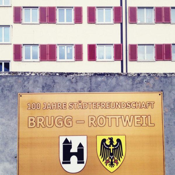 Vor einem Wohnhaus mit roten Fensterläden hängt an einer Betonwand ein bräunlich-goldenes Schild mit der Aufschrift Stätdepartnerschaft Brugg Rottweil. Darunter die Wappen der beiden Städte.