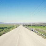 Helblau der Himmel auf der oberen Hälfte des Bilds darunter zartgrau flaches, hellgrünes Land und eine gerade, fluchtende Teerstraße.