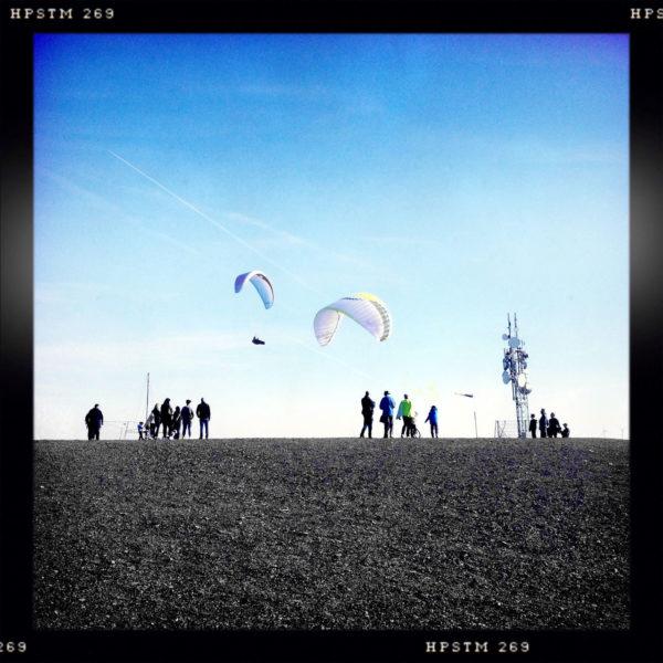 Das schwarz umrandete, quadratische Bild zeigt winzige Menschen als Silhouetten vor blauem Himmel am Horizont. Zwei Gleitschirme sind in der Luft.