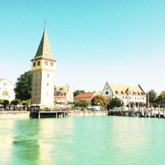 Cyanfarben bis weiß ist die Szene des Hafens von Lindau, betrachtet vom Boot aus über Wasser. Markant ragt ein Turm im linken Teil des Bilds.