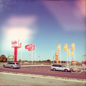 Ein Bild mit gelb-rosa Fehlfarbeneinflüssen zeigt einen Autorastplatz mit PKW, Tankstellenschild und Fahnen.