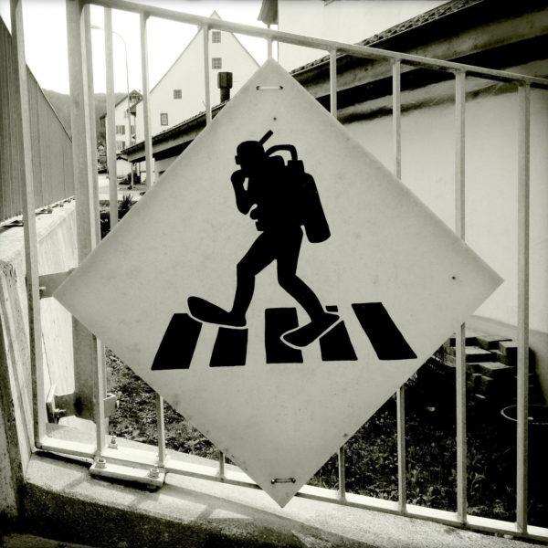 Ein quadratisches, auf der Spitze stehendes Schild an einem Zaun, auf dem ein Taucher skizziert ist, der über einen Zebrastreifen läuft.