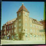 Ein stattliches Eckhaus mit quadratischem Türmchen als verfärbtes Bild im Retrostil. Der Bildrand ist schwarz-rosa-gelblich.