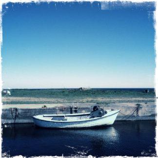 Längsseits betrachtet ein kleines, weißes Boot ohne Mast, das an einer Hafenmauer liegt. Der blaue Teint des Bildes zieht sich vom Hafenbecken über die Wiese bis ins offene Meer und den Himmel.