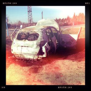 Ein ausgebranntes Autowrack, französischer Kleinwagen in Fehlfraben rötlich mit dickem schwarzem Bildrahmen.