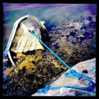 Ein gesunkenes Boot, dessen Bug aus dem Wasser steht liegt vertäut neben einem Felsen.